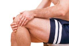 Mannen med knäet smärtar royaltyfri foto