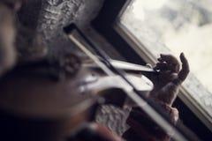 Mannen med länge spikar att spela en klassisk fiol med saknad stri Royaltyfri Fotografi