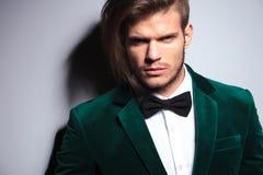 Mannen med långt hår som bär en elegant grön dräkt och halsen, bugar t Royaltyfria Bilder
