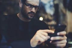 Mannen med mobiltelefonen som diskuterar idéer av partiplanläggningen som använder smartphonen, förband till radion 5G Royaltyfri Bild