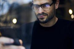 Mannen med mobiltelefonen som diskuterar idéer av partiplanläggningen som använder smartphonen, förband till radion 5G Royaltyfri Foto