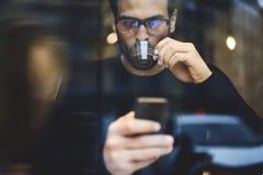 Mannen med mobiltelefonen som diskuterar idéer och, kräver för att projektera via smartphonen Royaltyfria Bilder