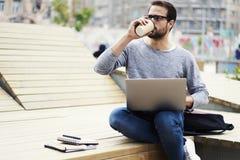 Mannen med mobiltelefonen som redigerar text för annonsering av den användande bärbar datordatoren, förband till radion 5G Arkivfoton