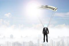 Mannen med pengar hoppa fallskärm flyg i himlen Royaltyfria Foton