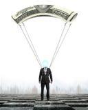 Mannen med pengar hoppa fallskärm landning på schackbrädejordning Royaltyfri Fotografi