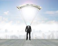 Mannen med pengar hoppa fallskärm landning på trägolv Arkivbild