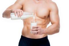 Mannen med perfekt hälla för kropp mjölkar in i ett exponeringsglas Arkivbilder