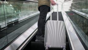 Mannen med resväskan står på den rörande rulltrappan, närbildsikt av ben lager videofilmer