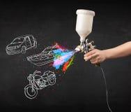 Mannen med retuschsprutasprutmålningsfärg med bilen, fartyget och motorcykeln drar Arkivbild