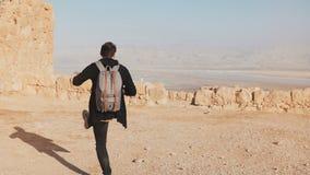 Mannen med ryggsäcken går på ökenbergöverkant Den tillfälliga journalistbloggeren tar foto av landskap för det döda havet Israel  arkivfilmer