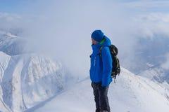 Mannen med ryggsäcken står på överkanten av berget i vinter Arkivfoton