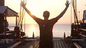 Mannen med ryggsäcken står på en pir med resninghänder under härlig solnedgång Begrepp av lycklig resor royaltyfria foton