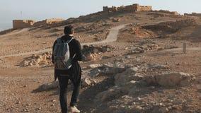 Mannen med ryggsäcken undersöker forntida fördärvar Den avkopplade Caucasian manliga turisten går på sommaröken vaggar och sand I stock video