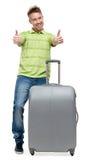Mannen med silverresväskan tummar upp royaltyfri bild