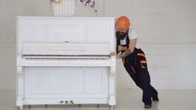 Mannen med skäggarbetaren i hjälm och overaller skjuter, försök att flytta pianot Laddaren flyttar pianoinstrumentet 308 mässings stock video