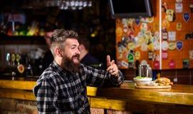Mannen med skäggdrinköl äter hamburgaremenyn Tyck om mål i bar Högt kalorimellanmål Hipster som kopplar av på baren Baren är royaltyfria bilder
