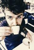 Mannen med skägget och mustaschen rymmer koppen kaffe, medan koppla av på kaféterrassen Grabben som den har, vilar med espressoka fotografering för bildbyråer