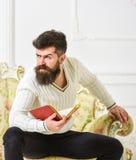 Mannen med skägget och mustaschen sitter på den barocka stilsoffan, håll bokar, vit väggbakgrund Reflexioner på litteratur arkivfoto