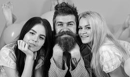 Mannen med skägget och mustaschen tilldrar blondin- och brunettflickor Flickanedgång som är förälskad med skäggig macho rosa bakg royaltyfria bilder