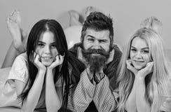 Mannen med skägget och mustaschen tilldrar blondin- och brunettflickor Flickanedgång som är förälskad med skäggig macho rosa bakg fotografering för bildbyråer