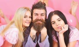 Mannen med skägget och mustaschen tilldrar blondin- och brunettflickor Flickanedgång som är förälskad med skäggig macho rosa bakg arkivfoton