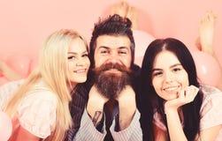 Mannen med skägget och mustaschen tilldrar blondin- och brunettflickor Flickanedgång som är förälskad med skäggig macho rosa bakg royaltyfri foto
