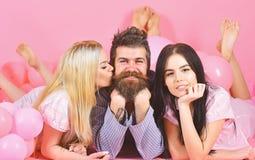 Mannen med skägget och mustaschen tilldrar blondin- och brunettflickor Threesomen på att le framsidor lägger nära ballonger Flick royaltyfri fotografi