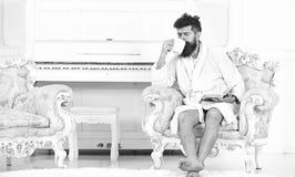 Mannen med skägget och mustaschen tycker om morgon, medan sitta på den lyxiga fåtöljen Elitfritidbegrepp Sömnig man in royaltyfri foto
