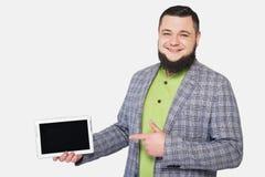 Mannen med skägget rymmer mobila enheten i hand Arkivbild