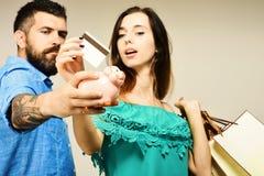 Mannen med skägget rymmer upp kreditkorten och spargrisen, slut Förälskad hållkreditkort för par på grå bakgrund royaltyfri foto