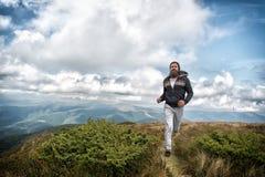Mannen med skägget tycker om frihet, körningar överst av berget Hipsteren känner sig fri, medan fotvandra, himmelbakgrund Man med Arkivbilder