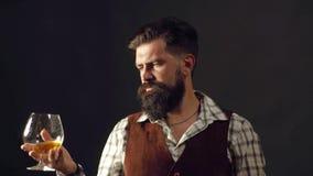 Mannen med sk?gget rymmer exponeringsglaskonjak Manbartendern med skägget rymmer exponeringsglaskonjak Alkoholbegrepp Stilfullt u stock video