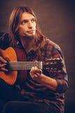 Mannen med skägget spelar gitarren Arkivfoto