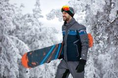 Mannen med skidar maskeringen som rymmer hans snowboard, extrema sport och winte Arkivfoto