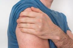 Mannen med skuldran smärtar rymmer hans mörbultade arm arkivfoto
