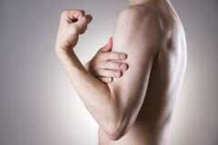 Mannen med smärtar i arm Smärta i människokroppen Fotografering för Bildbyråer