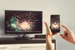 Mannen med Smartphone förband till en TV som håller ögonen på videopn hemmastatt Arkivfoto