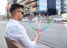 Mannen med smartphonen och zodiak undertecknar in staden Royaltyfri Fotografi