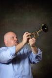 Mannen med starkt och fokuserat uttryck spelar en trumpet Royaltyfri Foto