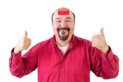 Mannen med tummar up och kreditkorten på pannan Royaltyfri Foto