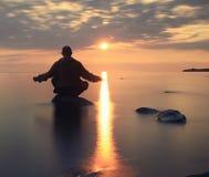 Mannen mediterar på sjön Royaltyfri Fotografi