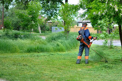 Mannen mejar gräs royaltyfri bild