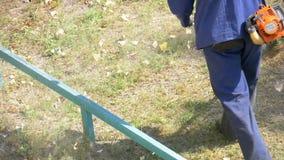 Mannen mejar gräs genom att använda en bärbar gräsklippare stock video