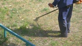 Mannen mejar gräs genom att använda en bärbar gräsklippare arkivfilmer