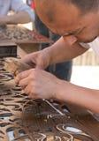 Mannen mejslar wood gravyr i seminarium nära den Chorsu basaren i Tas Royaltyfria Foton