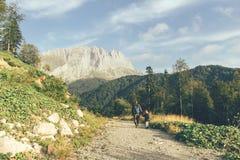 Mannen och barnet går på en vandring på en bergväg Landskap royaltyfri foto
