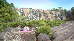 Mannen och den blonda kvinnan sitter bak på mattt bland landskap stock video