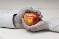 Mannen och den kvinnliga handen som rymmer ett äpple med älskar jag, dig inskriften Royaltyfria Bilder