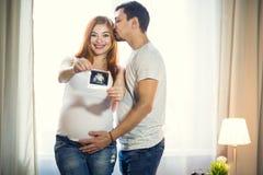 Mannen och en gravid ung kvinna väntar på ett barn hemmastatt b royaltyfri bild