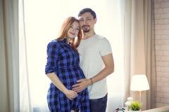 Mannen och en gravid ung kvinna väntar på ett barn hemmastatt b royaltyfri fotografi